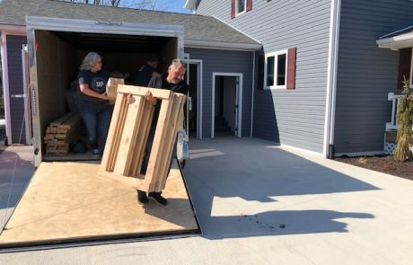 Levi King helps unload wooden materials used to assemble beds for The Farm Place.