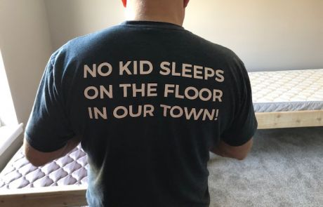 """Man from Sleep in Heavenly Peace assembling a bed, wearing a shirt that says, """"NO KID SLEEPS ON THE FLOOR IN OUR TOWN!"""""""