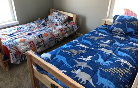 Fully assembled beds donated by Sleep in Heavenly Peace, with sheets, blankets, pillows, and comforters.