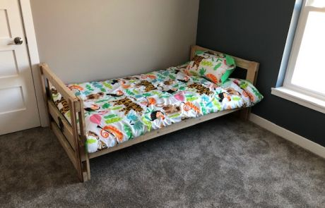 A fully assembled bed donated by Sleep in Heavenly Peace, with sheets, blanket, pillow, and comforter.