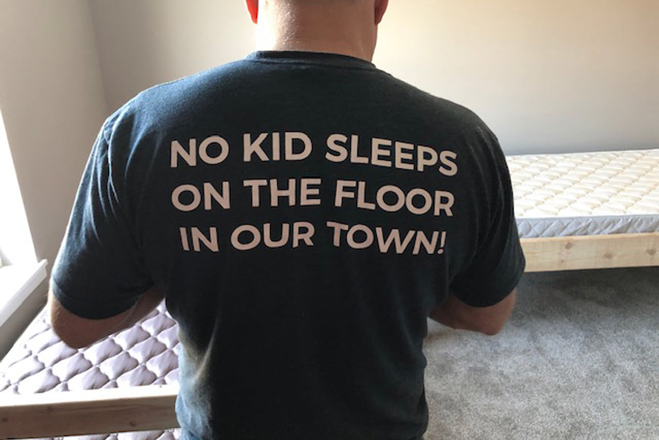 "Man from Sleep in Heavenly Peace assembling a bed, wearing a shirt that says, ""NO KID SLEEPS ON THE FLOOR IN OUR TOWN!"""
