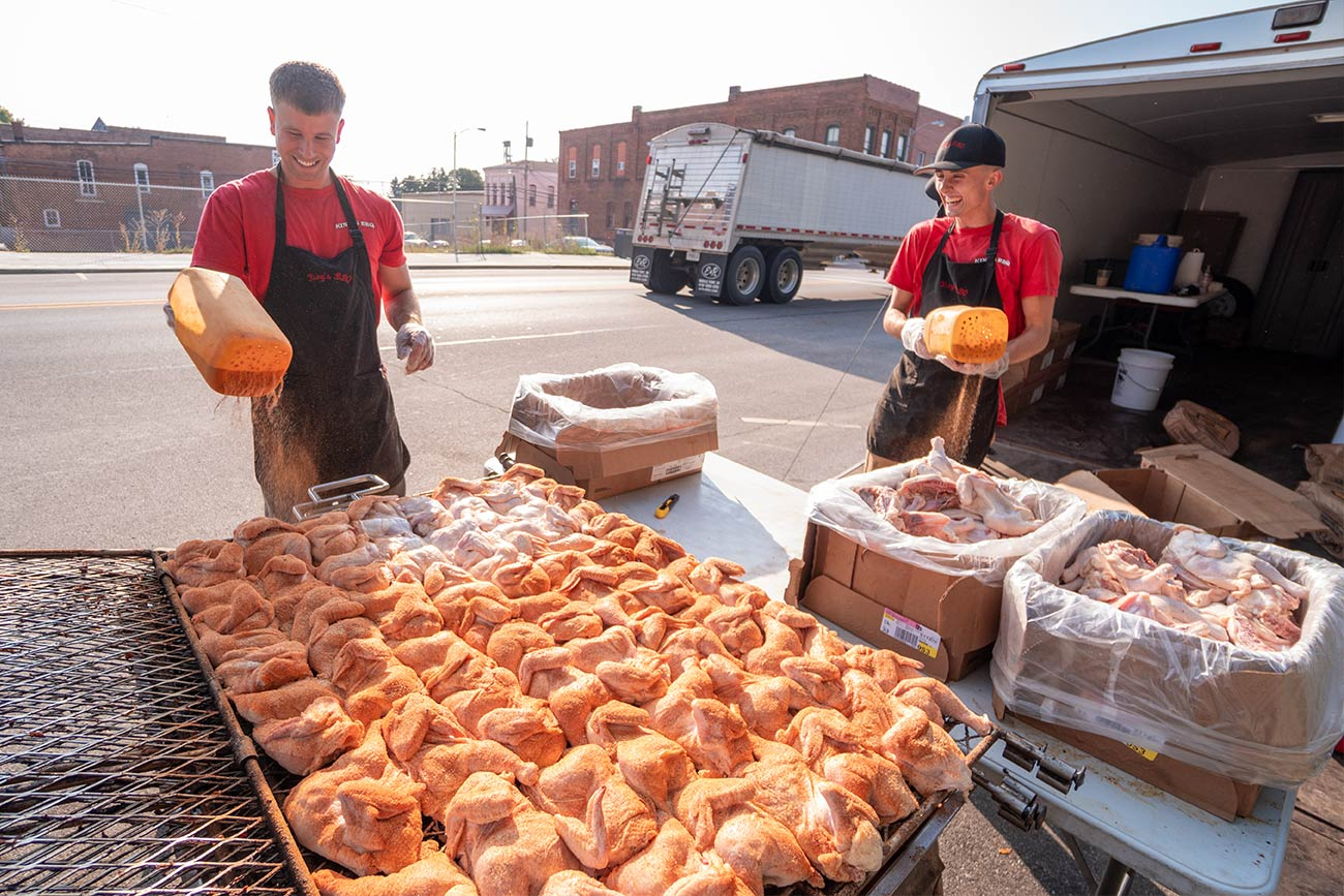 Workers from King's BBQ season chicken for The Farm Place's BBQ fundraiser