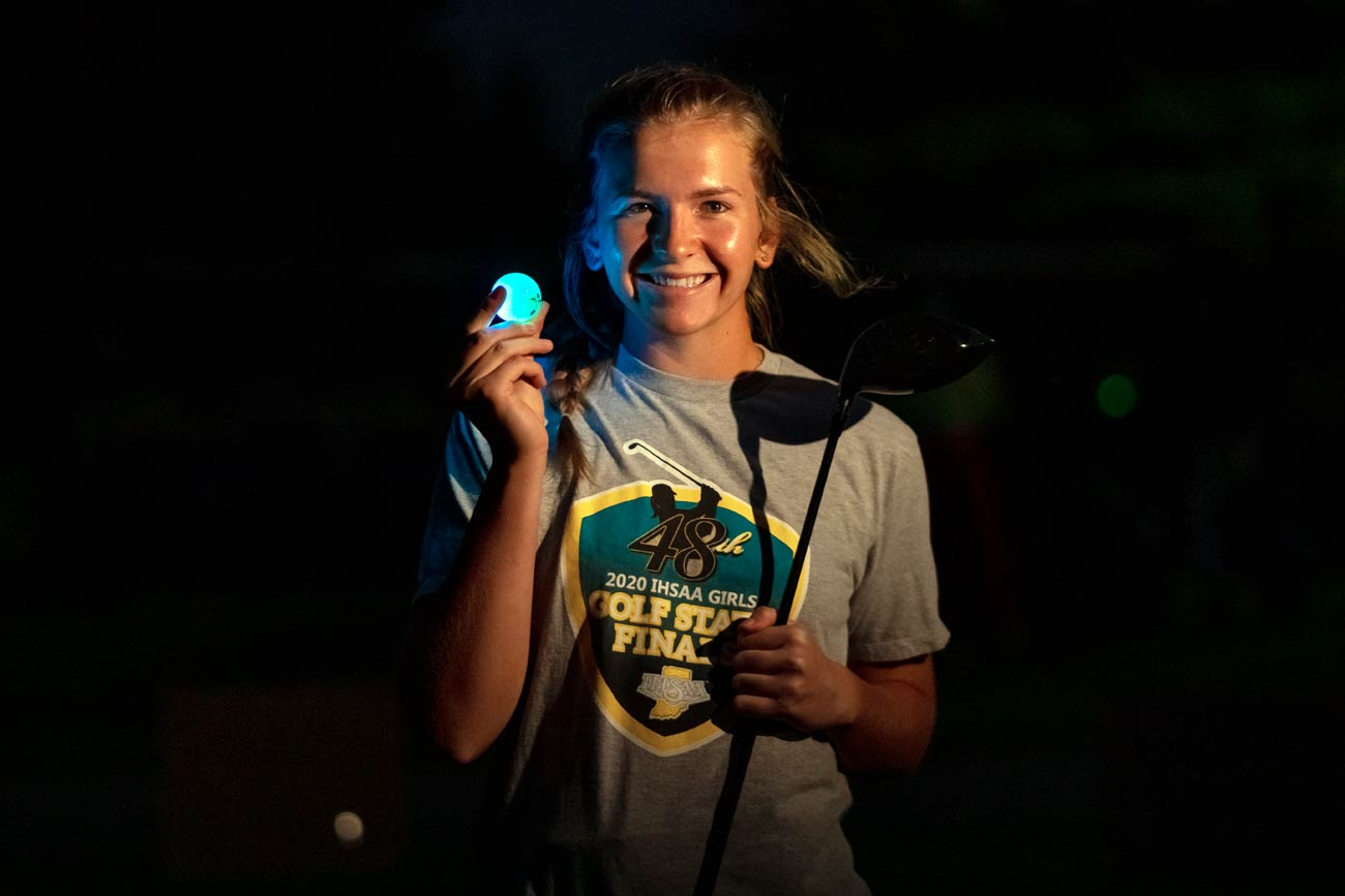 Tournament organizer Madison Keil holds a glow golf ball and driver in the dark.